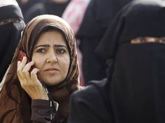An Egyptian woman talks on her cell phone as she waits to vote in Cairo, on May 23, 2012.
