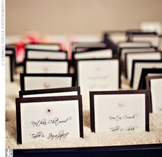 picture frames, laid down and filled with rice - escort cards wedged into the grains.