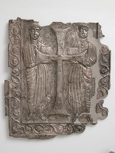 The two saints stand holding books and supporting between them a large cross. The youthful figure at the left and the bearded one at the right closely resemble early depictions of the evangelists John and Matthew. The plaque may have been a cover for a religious text.