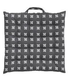 Seat cushion in organic cotton fabric with a printed pattern. Handle on one side. Polyester fill. Thickness 1 1/2 in.