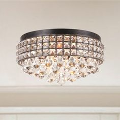 Add style and soft illumination to your entryway, dining room or any other area of your home with this Jolie iron and crystal flush-mount chandelier. The iron frame is finished in antique bronze and encircles a beautiful design of crystal beads.