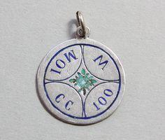 A silver pendant with blue enamel with a rebus spelling Aimez moi sans cesser (M MOI 100 CC), France, circa 1900.