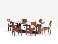 Francisque Chaleyssin: table de forme rectangulaire en chêne cérusé, loupe de myrte et aluminium, 74 x 200 x 100 cm (plus deux allonges de 84 cm), accompagnée d'une série de six chaises en chêne cérusé doré, h. 87 cm. Cette table présente un long plateau en loupe de myrte bordé d'aluminium, reposant sur quatre gracieuses sphères en bois noirci et sur deux montants pleins avec une entretoise basse à deux pans inclinés gainés de cuir rouge et d'aluminium.