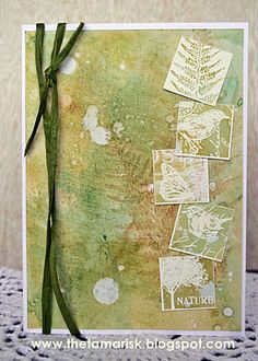 """By Teresa Abajo. Swipe a few Distress Ink pads onto a craft sheet, spritz with water, and swipe stamped cardstock through the ink. Stamp a large fern in brown; stamp again without re-inking. Flick water onto panel. Attach panel to white card base. Stamp 5 small images in VersaMark on separate piece of white cardstock. Heat emboss with clear powder. Cut into inch squares. Layer stamped squares onto 1 1/8"""" squares. Adhere to card. Add ribbon. Pretty!"""