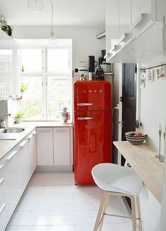 une cuisine laquée blanche avec un frigo rouge et meubles de cuisine blancs