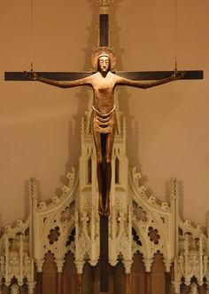 """Crucifix at Our Lady of Lourdes in London.  The artist, Dr. Imogen Stuart, herself says: """"My Christ is cruciform.  Christ is the Cross – symbol of salvation.  Saviour of people – embracing all humanity.  He is the Resurrection after suffering. The elongated body gives the figure an upsurging movement. The face acts as God's mystery and his revelation through Christ."""""""