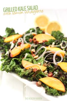 A delicious and summery Grilled Kale Salad with Lemon Vinaigrette! Topped with peaches, shallots and toasted hazelnuts, you will fall head over heels for this fun new recipe to get in your veggies!