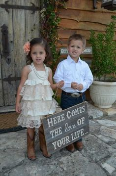 This flowergirl and ringbearer are wearing the cutest outfits for a country wedding! Also, that sign is fantastic!