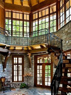 The rustic entry to this home sets the mood for what is to come. Wood inlaid into the stone floor marks the center around which the stairs and balcony are cantilevered off the walls