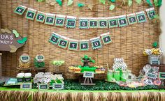 Jungle Themed Dessert Table: great use of rattan blinds and jungle fabric on the jars