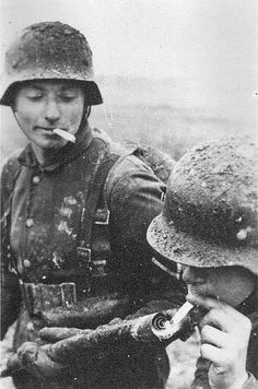 German soldier lighting his cigarette with a flamethrower somewhere on the eastern front.