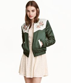 Green. Lightly padded satin pilot jacket with embroidered yoke, zip at front, and contrasting side pockets. Ribbed trim at neckline and elastication at