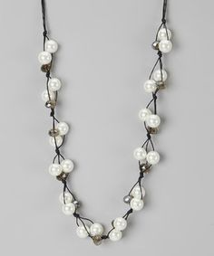 This extra-long necklace epitomizes everyday elegance with its shimmering strands of acrylic pearls laced in black cotton cording. Add a touch of class to an outfit with this timeless treat.