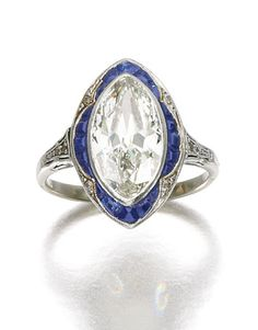 SAPPHIRE AND DIAMOND RING, CIRCA 1910.  Centring on a navette-shaped diamond within a scalloped surround of mixed-cut sapphires, accented with single-cut diamonds