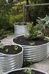 repurposed pipe raised bed - wonder if you could use the black plastic ones too.