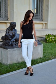 Classy and simple -  Asymmetrical black top, white pants along with nude and black heels