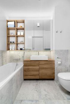 Kafle imitujące beton na podłodze, ścianach i w obudowie wanny okazały się idealnym tłem dla drewnianych mebli. Ładnie usłojone fronty szafki pod umywalką dodały wnętrzu przytulności. Praktycznym elementem wystroju jest regał na kosmetyki i ręczniki, umieszczony tuż nad wanną.