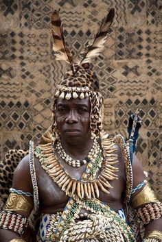 A royal guard of the Nyimi (King) of the Kuba people at his residence in Kinshasa, Democratic Republic of Congo (formerly Belgian Congo). The plume or feathers that one wears shows he has killed in the service of his King. They are also the royal executioners as well as bodyguards. 2008 | ©Greg Marinovic