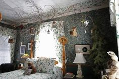 A spare bedroom with an outdoor theme, with an acorn bed, five different kinds of wallpaper and birdhouses hanging from real branches.