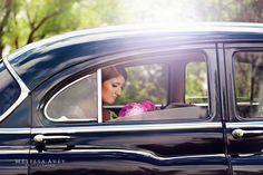 Artistic bridal portrait taken in a black vintage classic car. Melissa Avey Photography