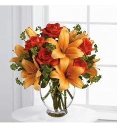 Floral bouquet/arrangement with dark orange roses and asiatic lilies are mixed with fresh green bupleurum and variegated pittosporum in a clear glass vase.