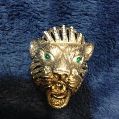 This is an amazingly beautiful cast metal silver tone roaring lions head brooch. The lion has green rhinestone eyes and white enameled fangs. (The enamel on the fangs shows some wear.) His top mane has rhinestones. His side manes are open design. This 3-dimensional brooch is 1 1/2 inches wide, about 2 1/2 inches long, and has a depth of 1 1/2 inches. Please note that the lighting makes the lion reflect back a yellow tone, but he is a shiny silver. Most of my vintage items and j...