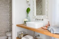 Stacked wood shelves shine against the white walls of the bathroom vanity. A stainless steel faucet mounted just below the gray floral mirror frame pours into a white, rectangular vessel sink. A gray patterned wallpaper creates an accent wall look in the connected toilet room.