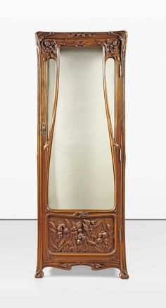 JEAN CANEPA A FINE ART NOUVEAU VITRINE, 1900 carved walnut, elaborately carved overall with sinuous stylised foliage and irises, the glazed door above a lower carved panel, flanked with conformingly carved and glazed sides 75.5/8 in. (189.5 cm.) high; 27.3/4 in. (70.5 cm.) wide; 14 in. (35.5 cm.) deep lower panel signed J. Canepa 1900.
