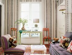 upholstered walls -- great funky furniture & oriental carpet & a classic white parsons table and coffee table for an elegant boho look