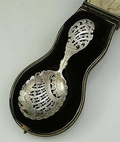"N4470 English Silver Pierced Spoon In Box    A fine English silver pierced spoon in the original fitted case. The handle and bowl are hand engraved between the intricate piercing. Length of spoon: 5 3/4""    Maker: James Dixon and Son Sheffield, 1900    Price: $450.00"