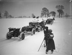 Anti-aircraft Bren gun team stands guard as 4.5-inch howitzers of the 1st Heavy Artillery Regiment (1st Polish Corps), towed by Morris-Commercial 'Quad' artillery tractors, passing by in deep snow, Scotland.