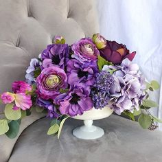 Purple wedding centerpiece with milk glass pedestal vase.