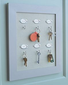Key Rack. Make a custom board from a piece of Homasote fiberboard cut to fit into a picture frame. Cover board with a piece of linen, and staple it at back. Tuck the board into the frame, then nail on labels and attach one screw hook for each set of keys.