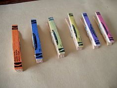 """Cute way to hang kids' art:  decoupage crayon wrappers to wood clothespins, hang heavy twine """"clothesline"""" onto a wall with push pins, and clip the art onto the line with these cute crayon pins!"""