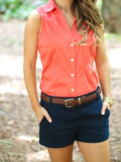 Coral sleeveless collared button down shirt paired with navy shorts and a brown braided belt.