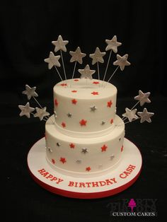 Buttercream base, white fondant ribbons at base of tiers, mini fondant red and silver stars with large fondant stars attached to wire. By Party Flavors Custom Cakes