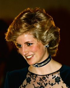 Princess Diana wears the earrings from the Saudi Sapphire and Diamond Suite, and a choker made from the suite's bracelet to a formal event,  the dress is in a dark blue velvet and lace.