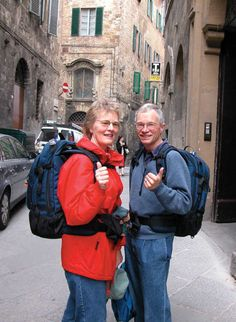 Couple Wearing Carry-On Packs How to travel to Europe.  Our first trip we carried way too much.  We looked like the second couple in this article.  We learned!