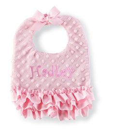 All pink minky bib is accented with grosgrain ruffles and bow at Velcro neck closure. Textured plush backing.