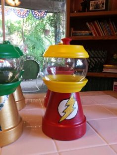 Clay pot gumball machine. Centerpieces for my daughter's Superhero Baby Shower.