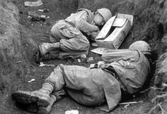 U.S. Marines try and catch some sleep at Khe Sanh during the Tet Offensive. Both men wear flak jackets and M1 helmets without covers. Scattered around them are various C ration components, most likely from their most recent meal, and it is possible to make out a C ration spoon as well as various cans and some of the paper packets containing condiments.