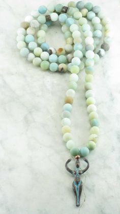 Goddess Mala Beads is made from 108 amazonite mala beads. It is completed with an antiqued goddess pendant. Mala for opening heart chakra.