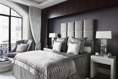 Dark silvery hues and geometric prints create a bold contemporary design with a masculine edge in the master bedroom. More of the rich wood paneling surrounds the wall.