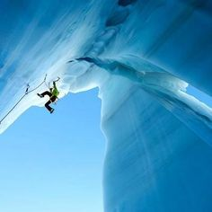 A beautiful shot of an athlete climbing steep turquoise ice.