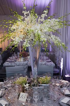 Sprays of white dendrobium orchids burst from the top of a tall glass centerpiece at an all silver table.