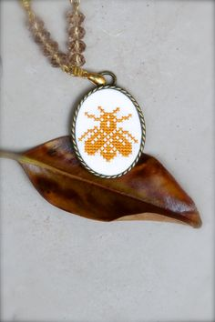 I love so much bees, these lovely hard-working creatures, that I created one more bee-themed necklace! The bee is cross stitched with honey-yellow