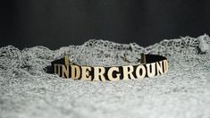 Finish off your look with this UNDERGROUND super cute letter Choker necklace.Take your outfit to the next level with this black wooden choker. * Length: 30 cm * Width: 2 cm * Chain link whit lobster clasp * Letters material: wood * Band material: elastic Available in black,red and white