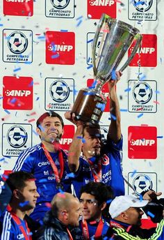 Footballers Jose Rojas (L) and Marcelo Diaz, of Universidad de Chile, celebrate with the rest of the team after winning Chile's Apertura tournament following a penatly shootout against O'Higgins, at the Nacional Stadium in Santiago, on July 2, 2012.