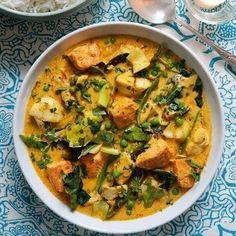 Thai fish curry 3 salmon fillets, skin removed 5 white fish fillets (eg cod or haddock), skin removed 2 tbsp sunflower or vegetable oil 4 spring onions, finely sliced 140g Thai red curry paste 1 tsp turmeric 2 x 400ml cans coconut milk 400ml fish stock 2 tsp golden caster sugar 2 lemongrass stalks, bashed Handful of kaffir lime leaves 150g green beans 150g peas 200g pak choi,
