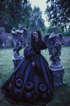 Creepy #Goth neo-Victorian in between two garden cherubs